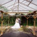 romantisch-bruidspaar-kijken-naar-elkaar-in-vervallen-kas-fotografie-door-ruwmantisch-nl-eline-kentie